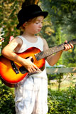 Little Music Man with Derby Hat. A young music maker man with a derby hat and a guitar standing by a tree. Shallow depth of field Stock Photo