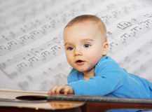 Little musician. Portrait of a little boy playing a guitar with a musical  background Royalty Free Stock Images