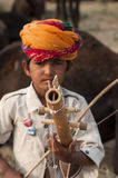 Little musician. A little boy playing music in Pushkar fair, India Stock Image