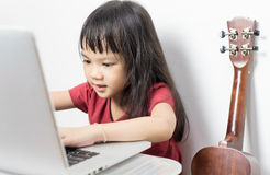 Little musician kid is working on her music on a laptop. Royalty Free Stock Photos
