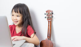 Little musician kid is working on her music on a laptop. Stock Photo