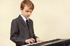Little musician in suit playing the electronic synthesizer Stock Photos