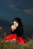 Little muslim girl on meadow before sunset