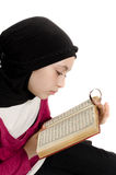 Little muslim girl reads Koran (Quran) stock images