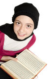 Little muslim girl reads Koran (Quran) royalty free stock image