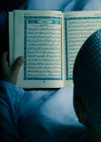 Little Muslim kid reading Quran at Ramadan night stock photography