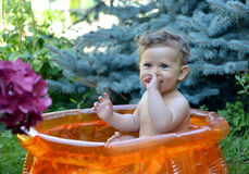 The little naughty girl sits in the inflatable pool in a garden Stock Image