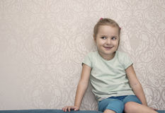 Little Naughty Girl. A naughty girl of six with a side gaze sitting on a sofa against the wall, indoor cropped portrait Royalty Free Stock Photography