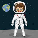 Little nerd boy astronaut standing on the moon surface on background of earth Royalty Free Stock Photography
