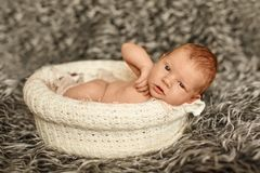 Little newborn baby is in the basket sleeping in blanket, lying. On bed royalty free stock image