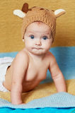 Little newborn baby with big eyes hat-knitting on a plain background. Stock Photos