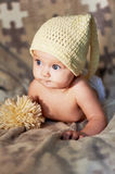 Little newborn baby with big eyes hat-knitting on a plain background. Stock Images