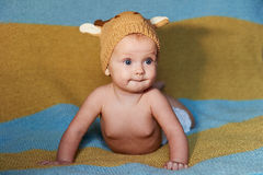 Little newborn baby with big eyes hat-knitting on a plain background. Royalty Free Stock Images
