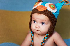 Little newborn baby with big eyes hat-knitting on a plain background. Royalty Free Stock Photography