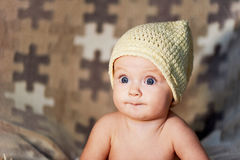 Little newborn baby with big eyes hat-knitting on a plain background. Royalty Free Stock Image