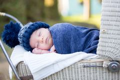 Little newborn baby boy, sleeping in old retro stroller in fores. T, autumn time, wrapped in scarf and knitted hat. Posed baby in retro pram, infant sleeping in Stock Photos