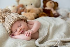 Little newborn baby boy, sleeping with teddy bear at home in bed. Infant resting with toy Stock Photo
