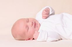 Little newborn baby boy sleeps. On beige background Royalty Free Stock Images