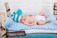 Little newborn baby boy sleeps. In a decorative wooden bed Royalty Free Stock Image