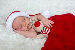 Little newborn baby boy, wearing Santa hat. And pants, holding toy, curiously smiling at camera Stock Photos