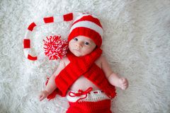 Little newborn baby boy, wearing Santa hat. And pants, holding toy, curiously smiling at camera Royalty Free Stock Photo
