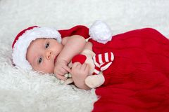 Little newborn baby boy, wearing Santa hat. And pants, holding toy, curiously smiling at camera Royalty Free Stock Images