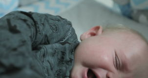 Little newborn baby crying. 4K Little newborn baby crying. Kid trying to shove a pacifier and foot in his mouth. Teeth climb the boy stock video footage