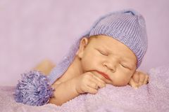 Little newborn baby in a funny hat sleeping in white blanket, lying on bed. Little newborn baby in a funny hat sleeping in white blanket, lying on bed royalty free stock photography