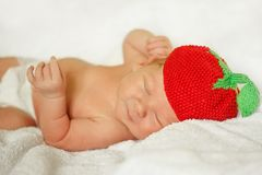 Little newborn baby in a funny hat sleeping in white blanket, lying on bed. Little newborn baby in a funny hat sleeping in white blanket, lying on bed stock photo