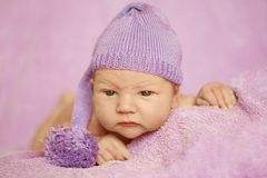 Little newborn baby in a funny hat sleeping in white blanket, lying on bed. Little newborn baby in a funny hat sleeping in white blanket, lying on bed stock image