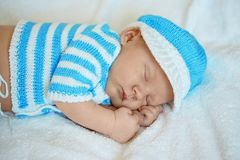 Little newborn baby in a funny hat sleeping in white blanket, lying on bed. Little newborn baby in a funny hat sleeping in white blanket, lying on bed stock photos