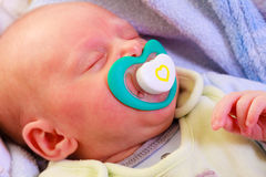 Little newborn baby girl 24 days sleeps. Closeup little newborn baby girl 24 days sleeping with dummy in mouth royalty free stock images