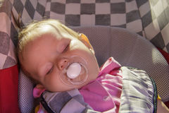 Little newborn baby girl rests in the car seat Royalty Free Stock Photos
