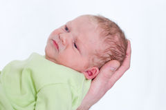 Little newborn baby on his fathers hand frowning royalty free stock photos