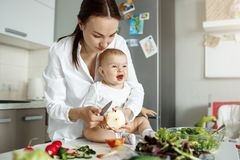 Little newborn baby sitting at table in front of mother with funny expression while mom cooking salad for family lunch Stock Image