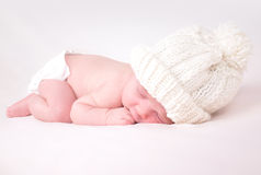 Little Newborn Baby Sleeping on White Background. A newborn baby is wearing a white hat and laying down sleeping on a soft white background. Use the photo to Royalty Free Stock Photography