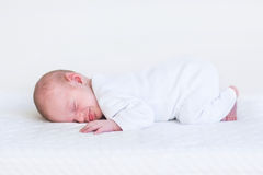 Little newborn baby sleeping on white blanket Stock Images