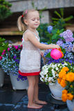 Little nice girl watering flowers with a Stock Photos