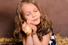 Little nice smiling girl hugging alive chicken Stock Photo