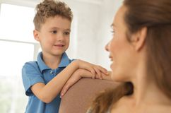 Little obedient son listening to his beautiful mother. Obedient son. Little cute dark-eyed obedient son feeling responsible while listening to his beautiful royalty free stock photos