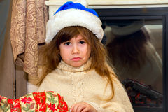 Little offended girl unwraps a gift. Royalty Free Stock Images