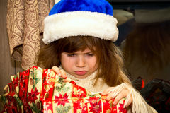 Little offended girl unwraps a gift. Stock Photos
