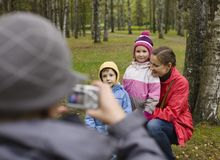 Little offspring shooting his family in park. Outside autumn Stock Images