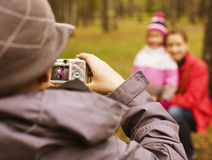 Little offspring shooting his family in park outside. Spring nature Royalty Free Stock Images