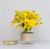 Little old book, a bouquet of flowers chrysanthemums, goldenrod and daisies in a glass vase homemade. On gray background closeup Royalty Free Stock Photo