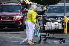 Little old ladies in the supermarket parking lot with a shopping cart and a musician playing for tips in the background. Tulsa OK USA 6 2 2018 Little old ladies stock photo