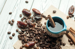 A little old pottery handmade cup of coffee, coffee beans, sweet dried dates and cinnamon sticks Royalty Free Stock Images