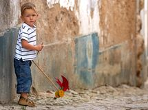 Little one with handmade toy. Cute 3-years old blond boy in casual clothes playing with handmade toy outdoors, old wall on background Royalty Free Stock Images