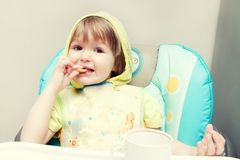 A little one-year-old baby girl is eating at highchair. Royalty Free Stock Images