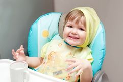 Little one-year-old baby girl is eating at the highchair. Royalty Free Stock Image